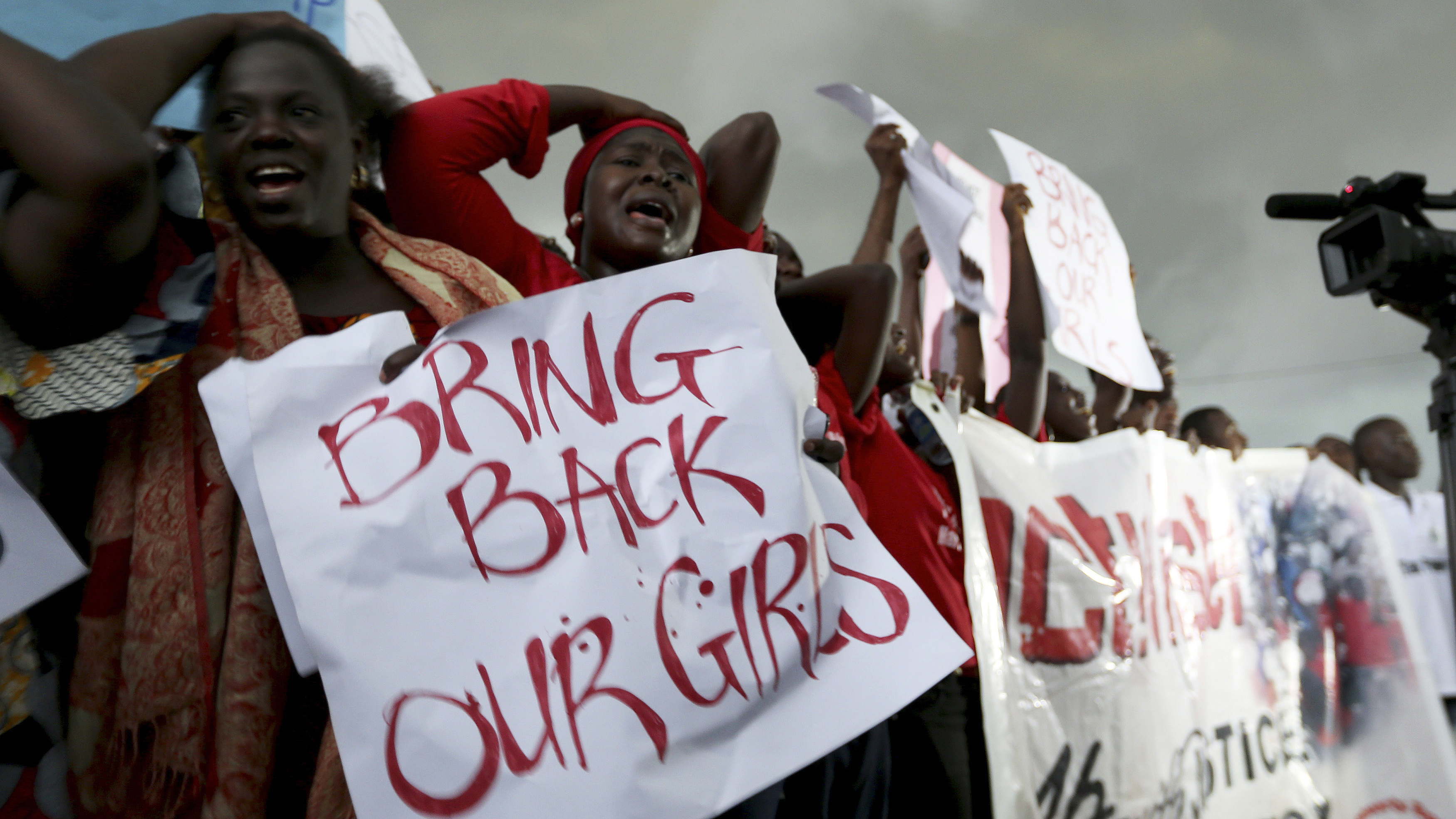 Women react during a protest demanding security forces to search harder for 200 schoolgirls abducted by Islamist militants two weeks ago, outside Nigeria's parliament in Abuja April 30, 2014. Scores of suspected Boko Haram gunmen stormed an all-girls secondary school in the village of Chibok, in Borno state, on April 14, packing the teenagers onto trucks and disappearing into a remote, hilly area along the Cameroon border. REUTERS/Afolabi Sotunde (NIGERIA - Tags: CIVIL UNREST RELIGION EDUCATION TPX IMAGES OF THE DAY) - RTR3NB21